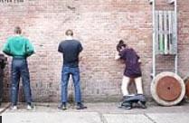 Frau pisst mit Männern an eine Wand