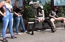 Mädchen pinkeln an einer Haltestelle
